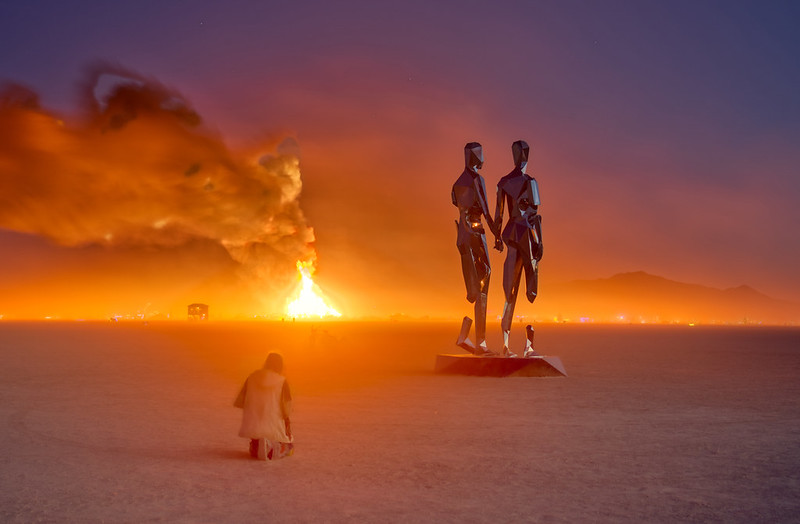 Burning Man 2019 statue and fire in distance