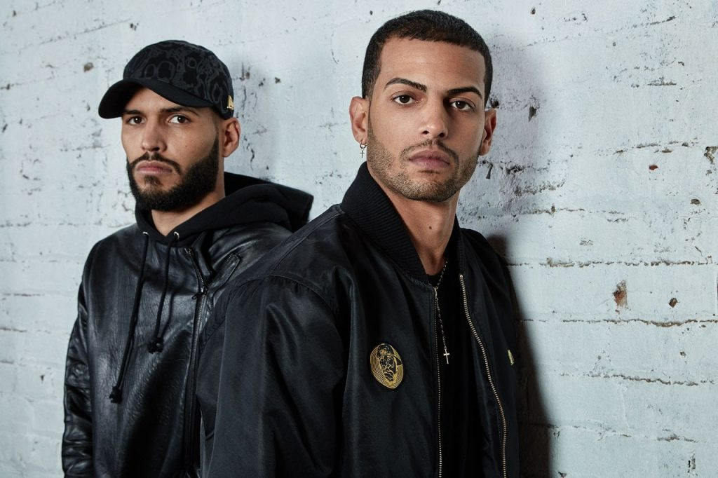 The Martinez Brothers against a white brick wall